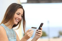 Happy woman buying online with a smart phone.jpg