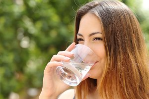 Happy woman drinking water from a glass outdoor.jpg