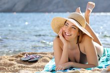 Happy woman thinking and looking at side lying on the beach.jpg