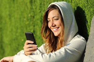 Modern teenager girl using a smart phone in a park.jpg