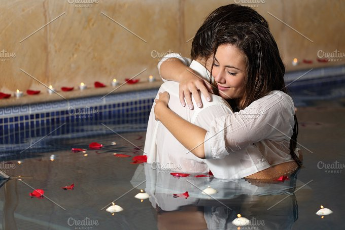 Romantic couple hugging in a pool with candles and rose petals.jpg - People