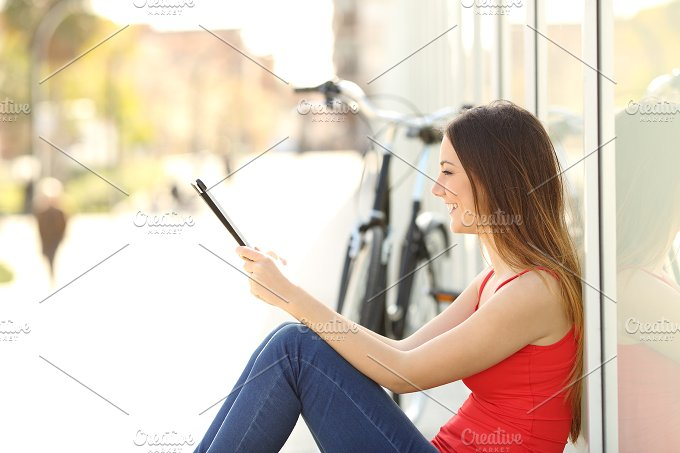 Teen girl using a tablet sitting in the street.jpg - Technology