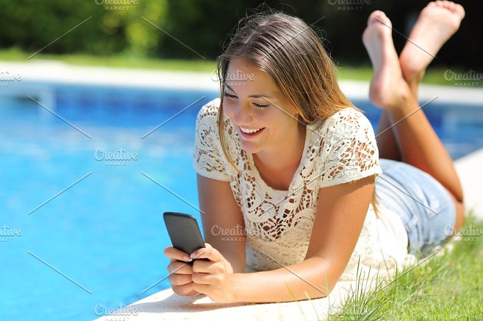 Teenager girl using a smart phone resting on a pool side.jpg - Technology