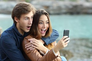 Shocked couple watching a smart phone on holidays.jpg