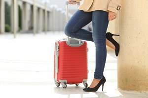 Tourist woman legs waiting with a suit case in an airport.jpg