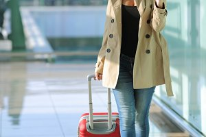 Traveler woman walking and using a smart phone in an airport.jpg