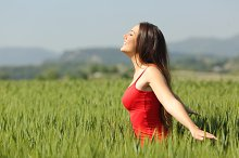 Woman breathing fresh air in a meadow and touching the wheat.jpg