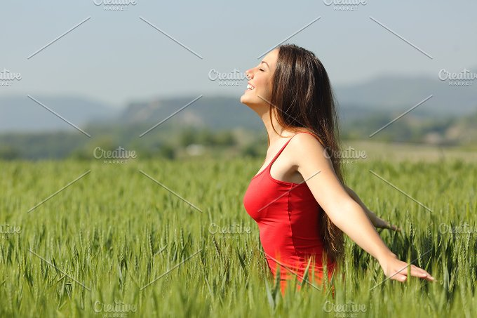 Woman breathing fresh air in a meadow and touching the wheat.jpg - Health