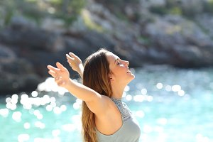Woman breathing fresh air raising arms on holidays.jpg