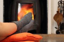 Woman feet with socks resting near fire place.jpg