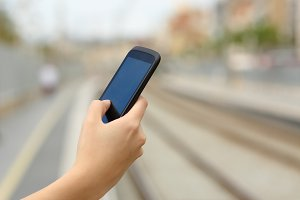 Woman hand holding a smart phone in a train station.jpg