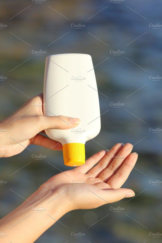Woman hands applying sunscreen from a sunblock bottle.jpg - Health