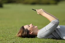 Woman using a smart phone resting on the grass in a park.jpg