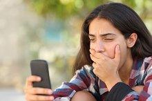 Worried teenager girl looking at her smart phone.jpg
