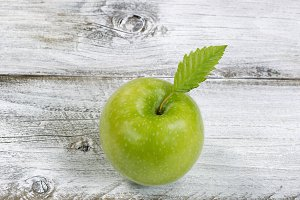 Lovely green apple on old wood