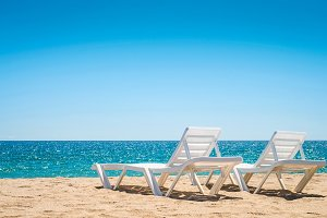 Two chaise-longues on the beach