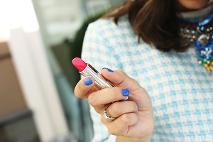 Bright pink lipstick in the hands