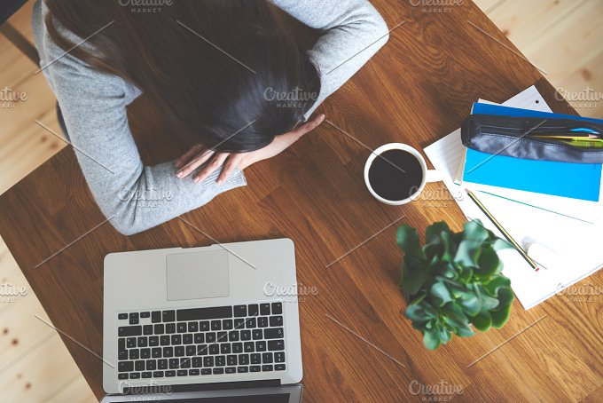 View down of woman sitting at table in home office with head resting on hands.jpg - Education