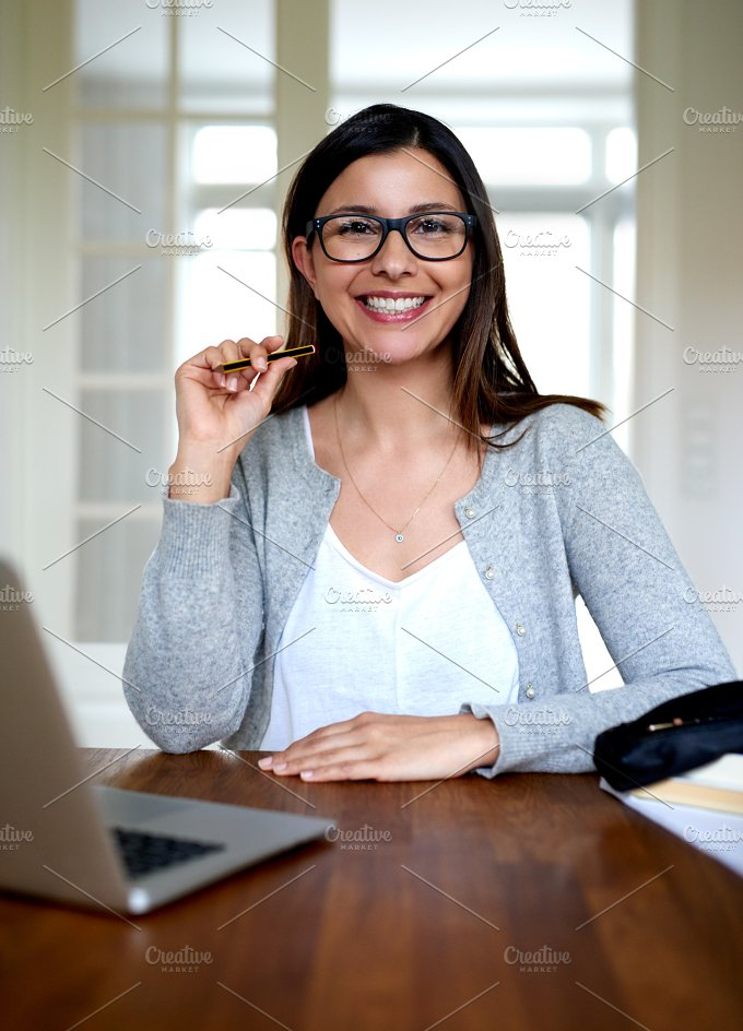 Woman sitting upright smiling at home office desk..jpg - Education