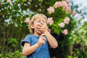 Boy blowing nose in front of