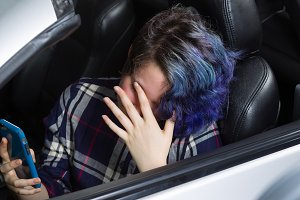 Depressed Teen girl in car with cell