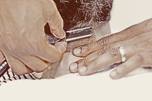 male hands shaving a beard