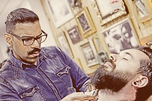 barber on a beard shaving session