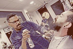 young barber spraying a beard