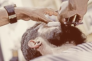 young male hands shaving a beard