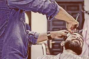 male hairstylist on a beard shaving