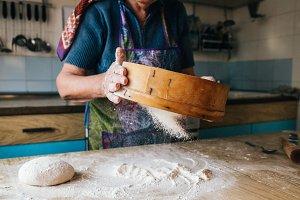 grandma sifting flour on the dough