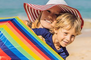 Mother and son on the beach in a hat
