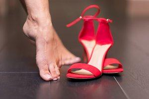 Woman taking off red high heel sanda