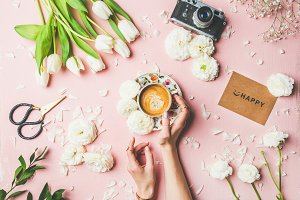 Female hands holding coffee, flowers