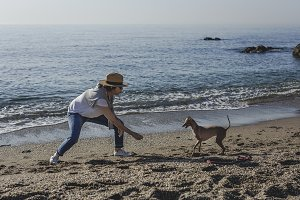 Woman playing with dog on the beach