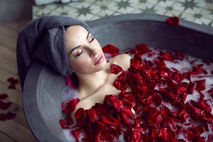 beautiful girl lying in a stone bath