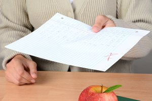 Apple on Books Teacher Handing Paper