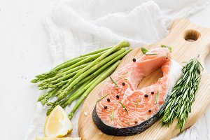 Raw salmon steak with asparagus