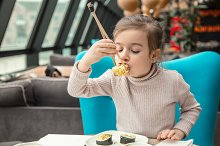 little girl eating sushi by  in People