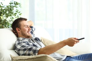 Happy man relaxing watching tv at ho