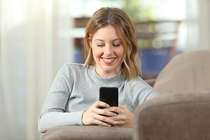 Happy lady texting on phone on a cou