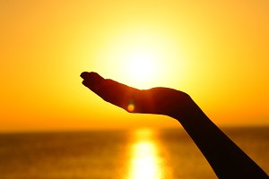 Woman hand holding sun at sunset on