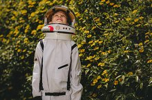 Cute boy in astronaut dress playing by  in People