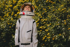 Cute boy in astronaut dress playing