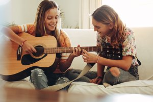Girls learning to play guitar