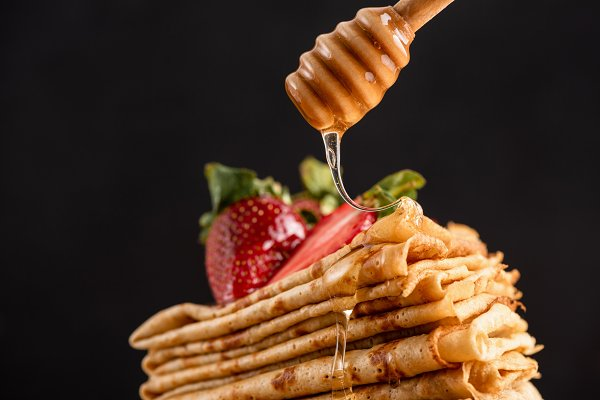 Stock Photos: The baking man - Honey pouring on crepes or blini