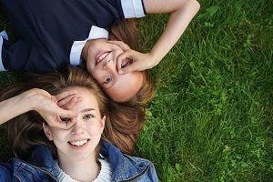 Sisters lie on green lawn.