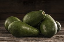 Ripe shiny avocados in heap by  in Food & Drink