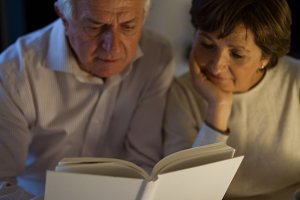 Senior couple reading a book in home