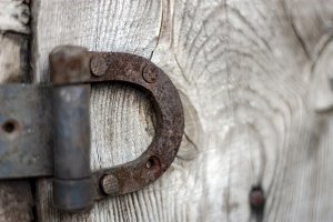 Rusty hinge on a wooden old fence